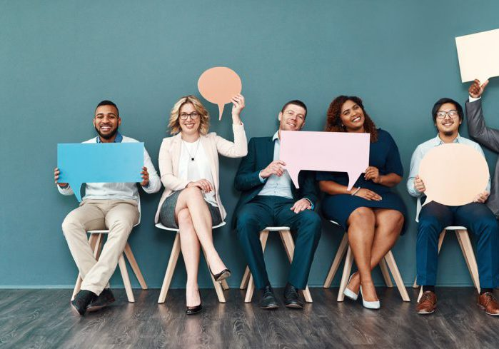 Shot portrait of a diverse group of businesspeople holding up speech bubbles while they wait in line